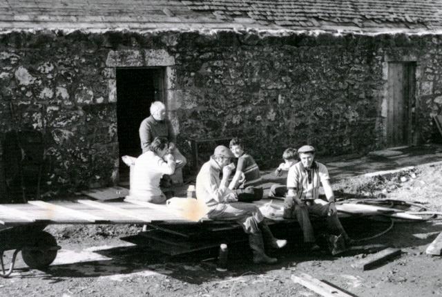 Some children sitting in a farmyard