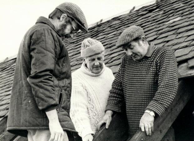 Three men mending a cart